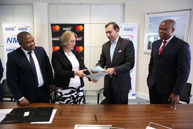 NMB Managing Director – Ineke Bussemaker exchanging partnership contracts with Mastercard President for Middle East and Africa – Raghu Malhotra at a press signing ceremony held in Dar es Salaam today. The partnership will pave way for digitization of the agricultural sector in Tanzania with the rollout of eKilimo, a mobile solution developed by the MasterCard Lab for Financial Inclusion. Looking on the left is the NMB Acting Chief Retail Banking – Abdulmajid Nsekela and right is the Mastercard Division President Sub-Saharan Africa – Daniel Monehin.