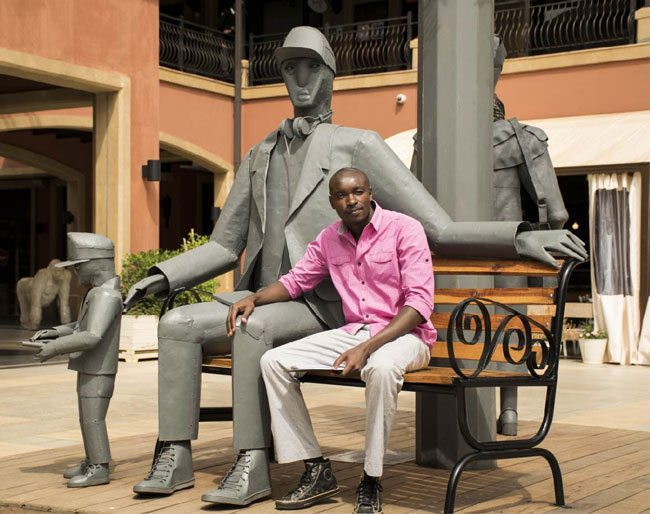 Peter Ngugi poses next to his newly revealed monumental sculpture at The Hub Karen.